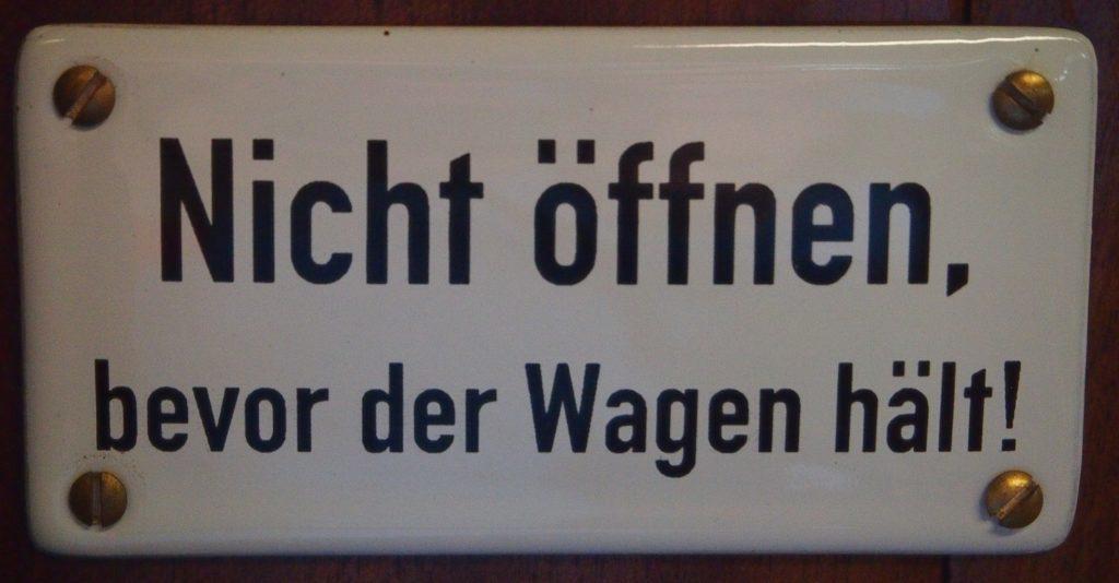 """Ausnahmen - Schild mit der Aufschrift """"Nicht öffnen, bevor der Wagen hält!"""""""