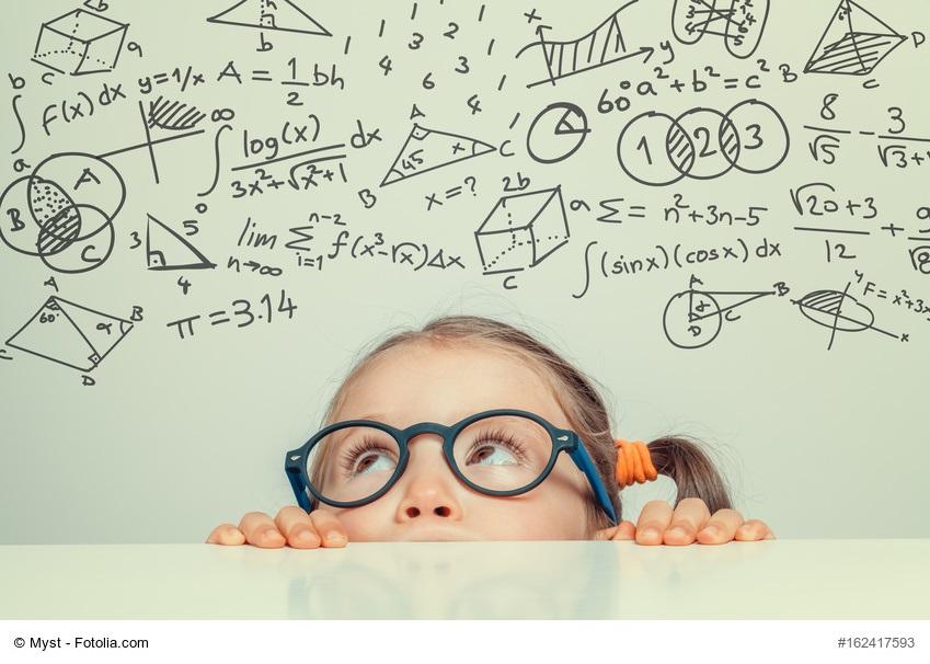 Abwiegen, notieren und berechnen - kleines Mädchen starrt auf mathematische Formeln