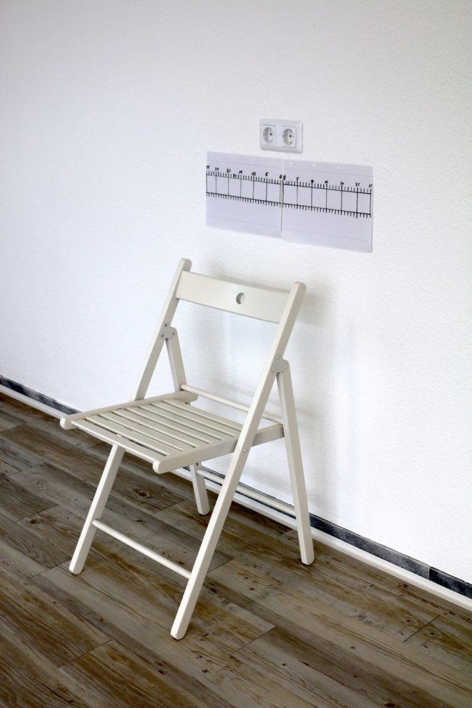 Selbsttest Beweglichkeit - Stuhl mit beschriebener Messlatte dahinter